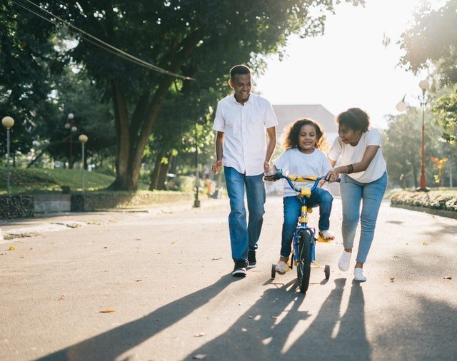 A family helping their child ride a bike - Individual health insurance